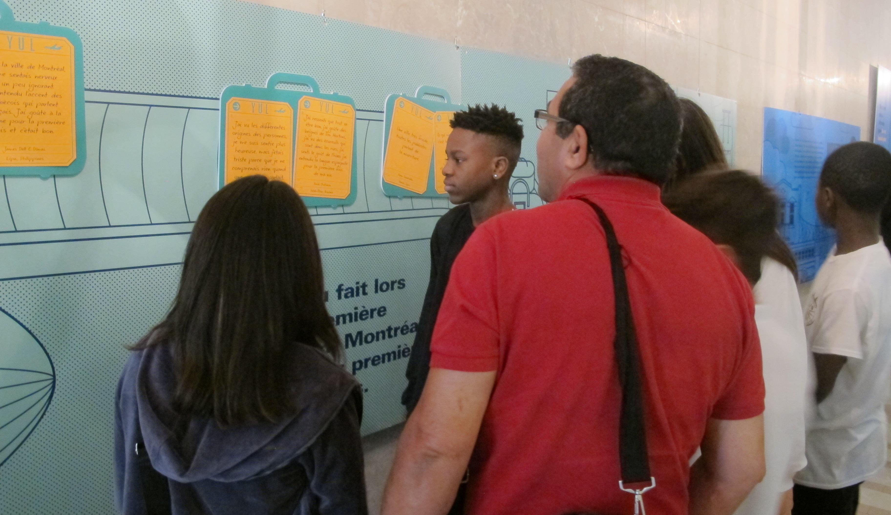 Des élèves et un enseignant devant un panneau de l'exposition